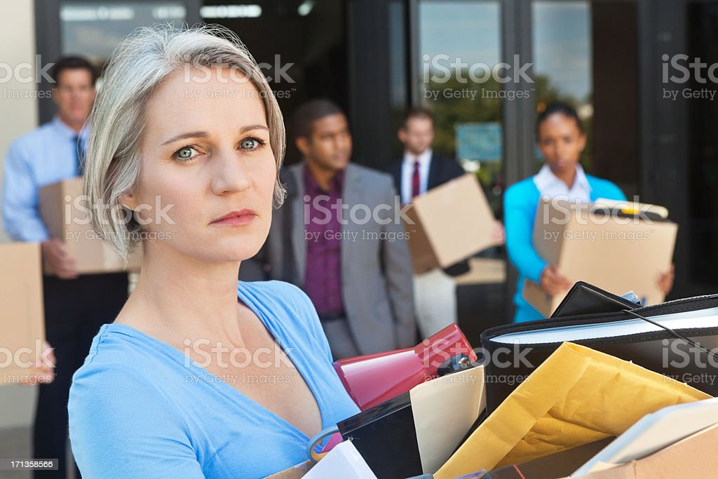Mature woman leaving office after being fired or laid off stock photo