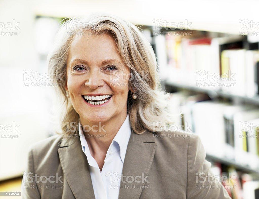 Mature woman librarian looking at camera. royalty-free stock photo