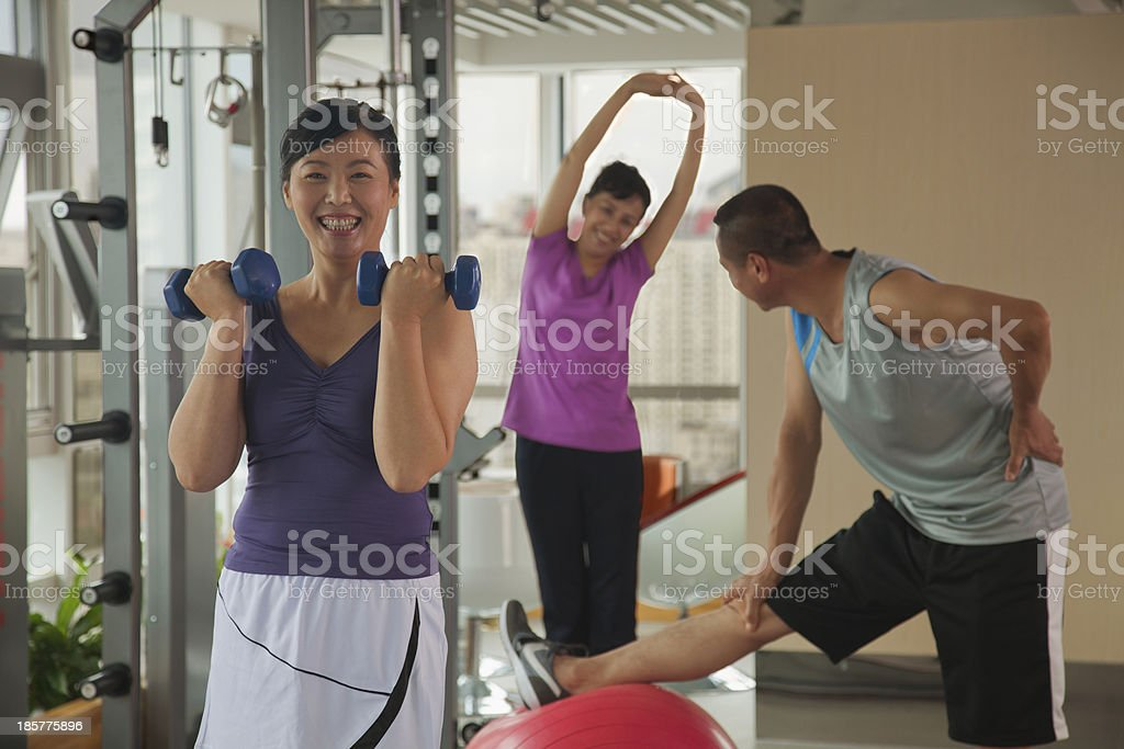 Mature woman lifting weights in the foreground royalty-free stock photo