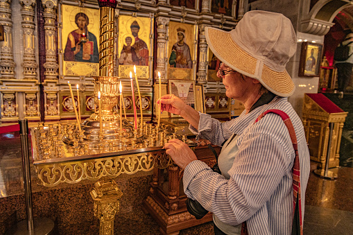 Mature woman lights a candle in theChurch on Blood in Yekaterinburg,Sverdlovsk Region,Ural,Russia