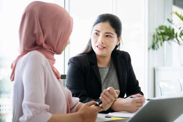 Mature woman listening to female colleague Two businesswomen in office, woman in 40s looking towards women wearing hijab southeast asian ethnicity stock pictures, royalty-free photos & images