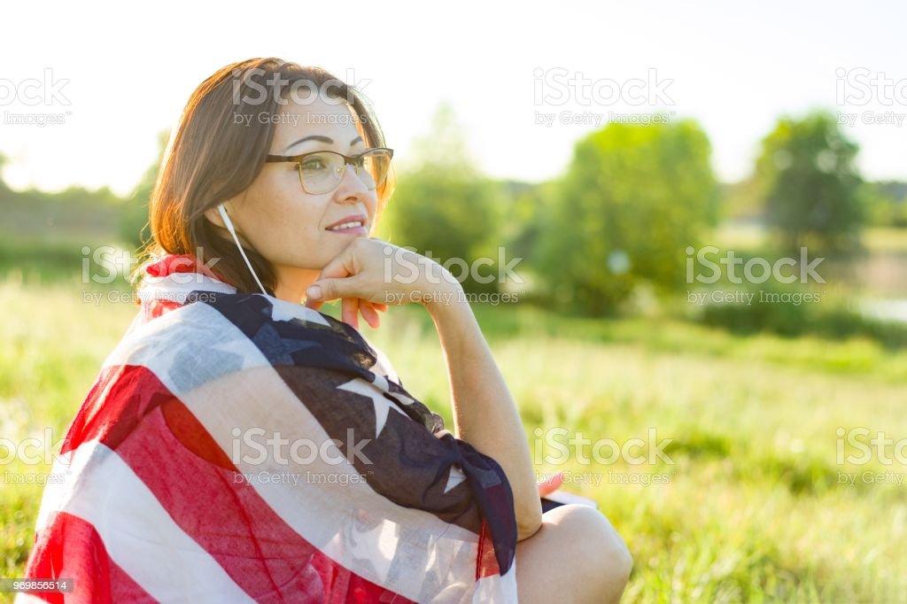 Mulher madura escuta a música, um audiolivro em fones de ouvido, relaxa na natureza. Sobre os ombros de bandeira americana - foto de acervo