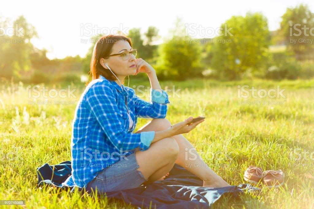 Mulher madura escuta a música, um audiolivro em fones de ouvido, relaxa na natureza. - foto de acervo