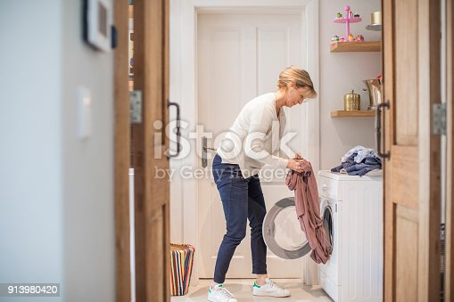Side view of mature woman loading clothes in washing machine. Full length of female is doing daily chores. She is wearing casuals at home.