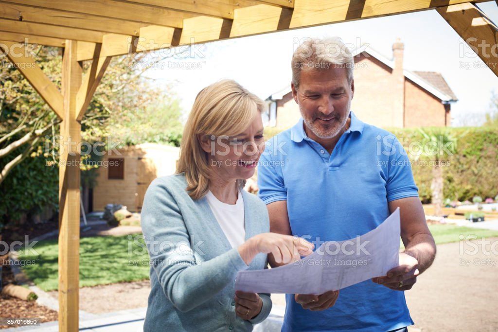 Mature Woman Looking At Design Plan With Landscape Gardener stock photo