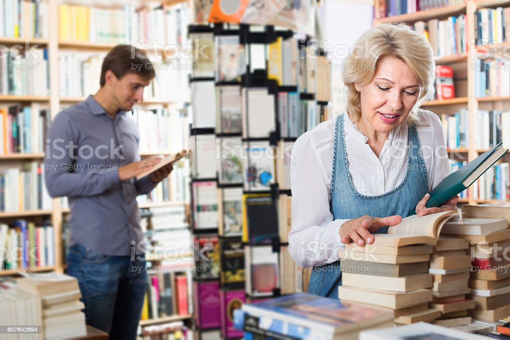 Mature woman looking at open book in hands stock photo