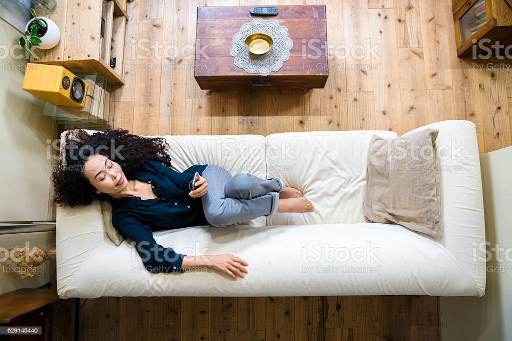 Mature woman looking at smartphone while lying on a sofa stock photo