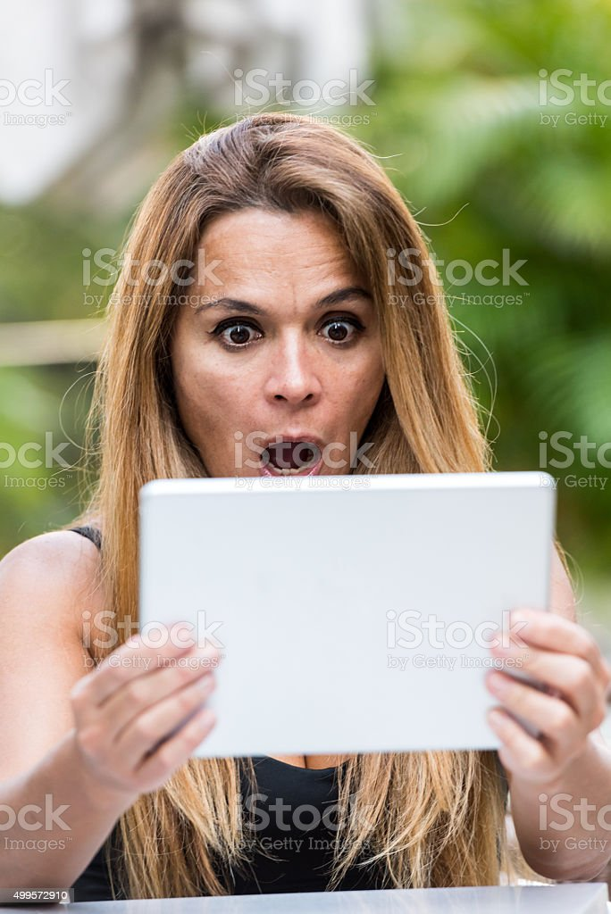 Mature woman looking at tablet in disbelief stock photo
