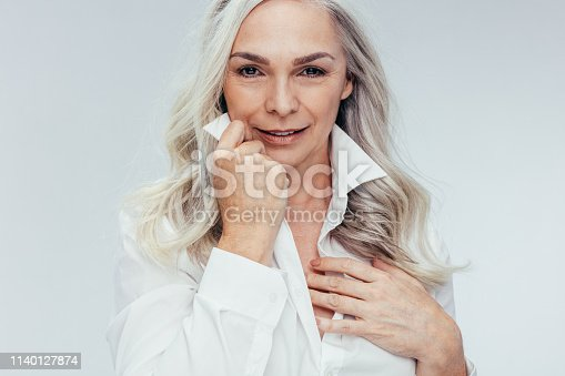Attractive mature woman posing against white background. Senior woman looking attractive in white shirt.