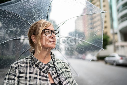 Mature woman looking away using umbrella outdoors