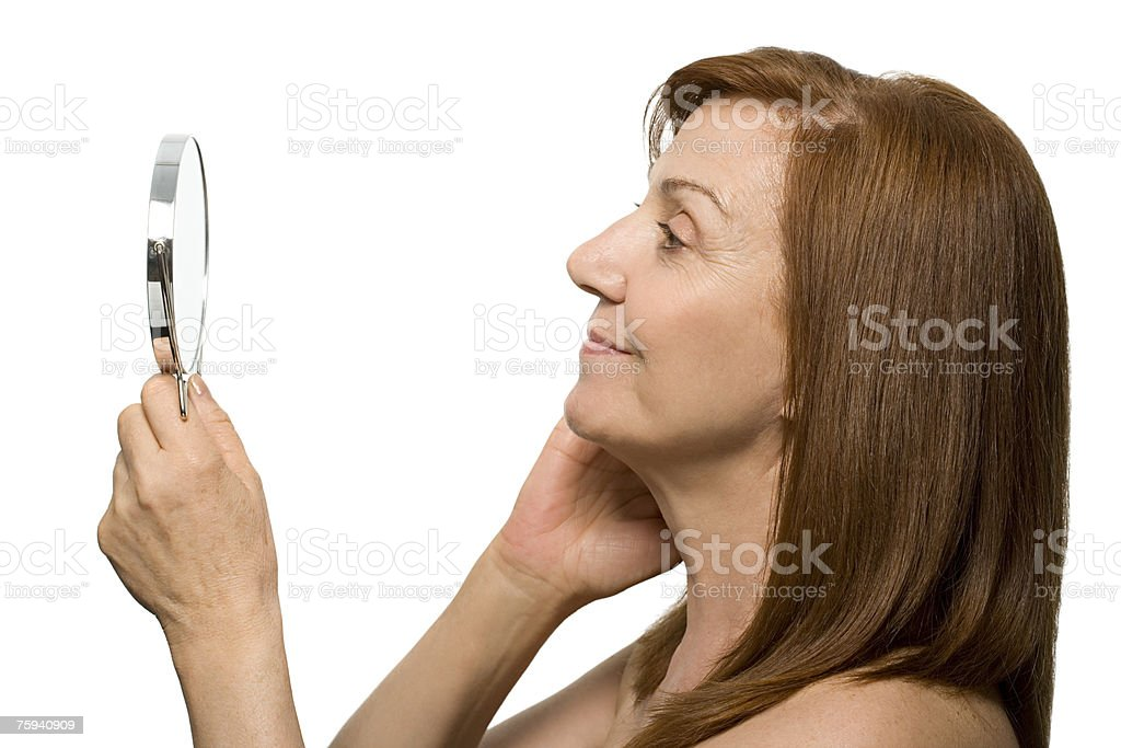 Mature woman looking in hand mirror stock photo