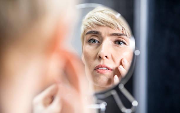 성숙한 여자 찾고 에 거울 감동 얼굴 서 에 욕실 - 주름 뉴스 사진 이미지