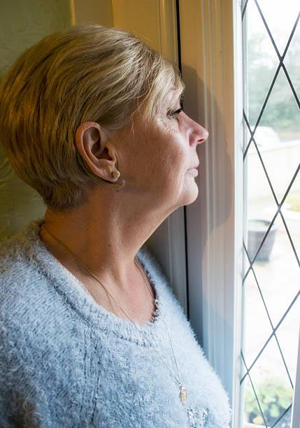 femme d'âge mûr en regardant par la fenêtre - indiscret photos et images de collection