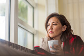 istock Mature woman looking out the window feeling sad. 1191047617
