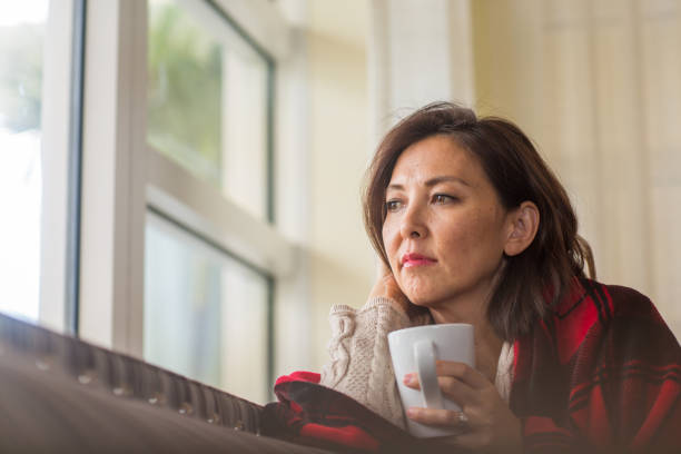 Mature woman looking out the window feeling sad. stock photo