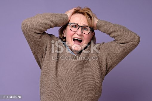 Mature woman looks at camera holding head in hands feels unhealthy stressed. Grandmother suffers from headache or migraine. Negative facial human emotion.