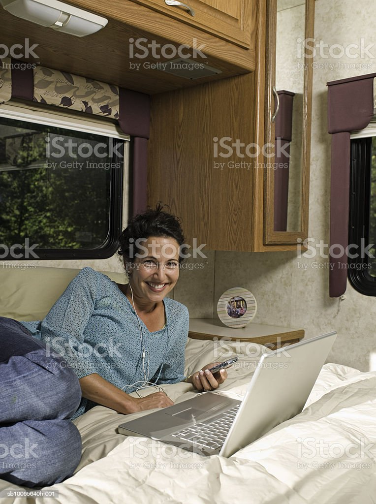 Mature woman lying on bed in motorhome, listening music, smiling, portrait foto de stock libre de derechos