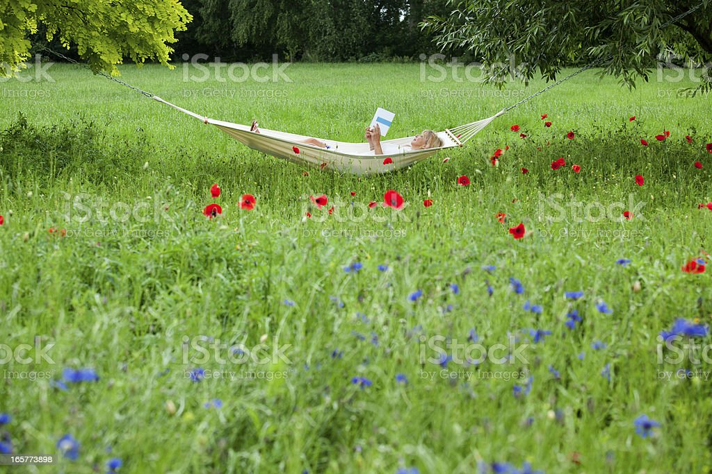 Mature woman lying on hammock in garden reading book royalty-free stock photo