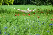 Mature woman lying on hammock in garden reading book