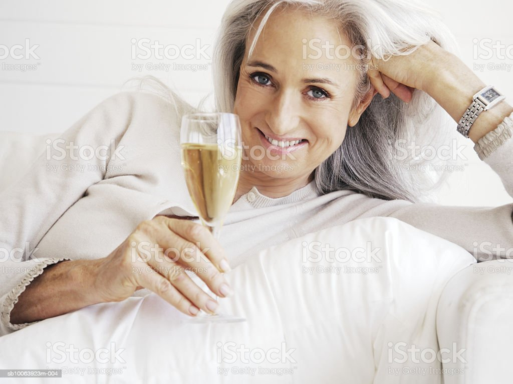 Mature woman lying on sofa, holding champagne glass, smiling, portrait Lizenzfreies stock-foto
