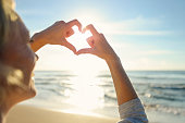 Mature woman making a heart shape with her hands on the beach. She is smiling and happy. Probably on a romantic vacation. The ocean is in the background. Copy space