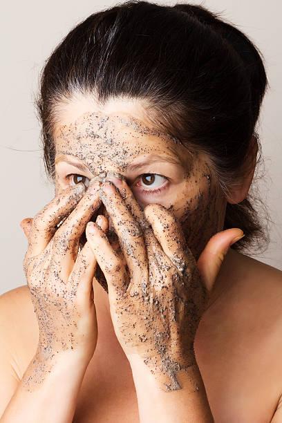 ältere frau ist kosmetische maske - kaffeepeeling stock-fotos und bilder