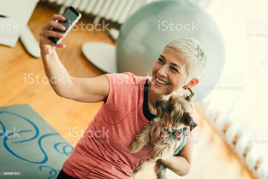 Mature Woman Making Selfie With Her Dog At Home. stock photo