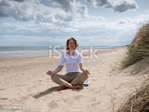 Mature woman meditating in Lotus Pose on the beach under a dramatic sky. Knokke, Belgium.
