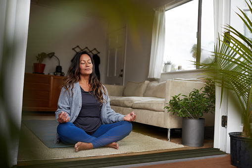 Serene mature woman meditating with her eyes closed while practicing yoga on the floor of her living room at home