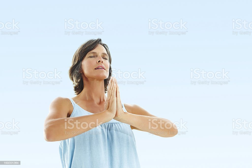 Mature woman meditating with eyes closed against sky royalty-free stock photo