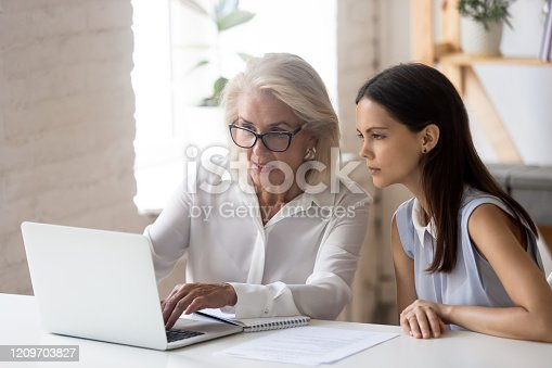 926404274 istock photo Mature woman mentor explain intern corporate application seated at desk 1209703827