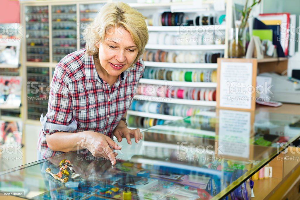 Mature woman near glass showcase in boutique royalty-free stock photo