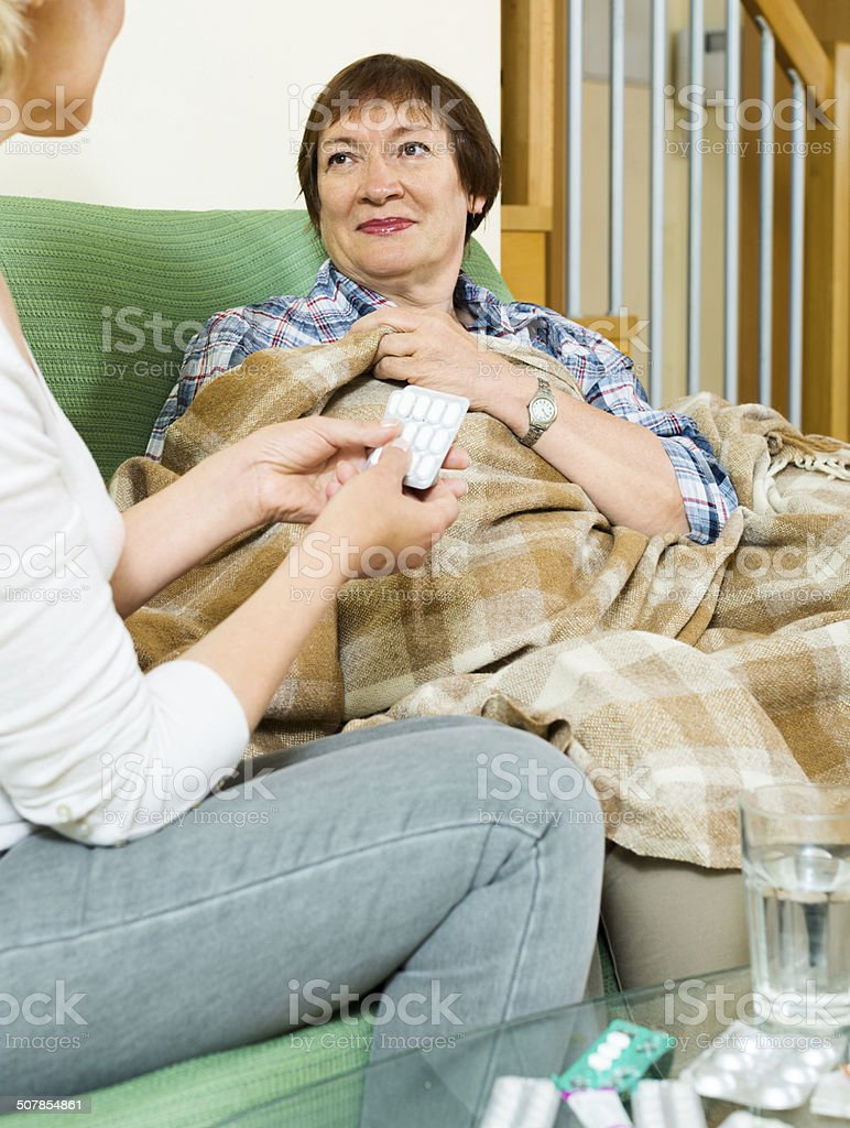 Mature woman offering medicine and water to pensioner stock photo