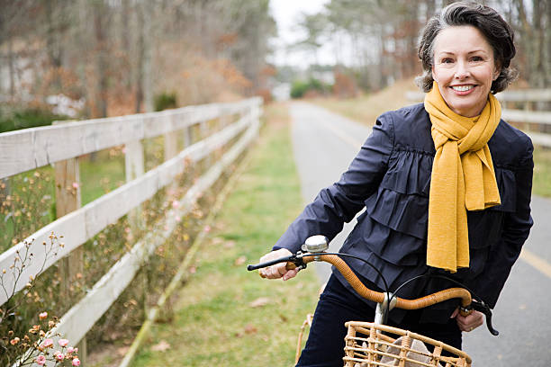 mature woman on a bicycle - baby boomers stock pictures, royalty-free photos & images