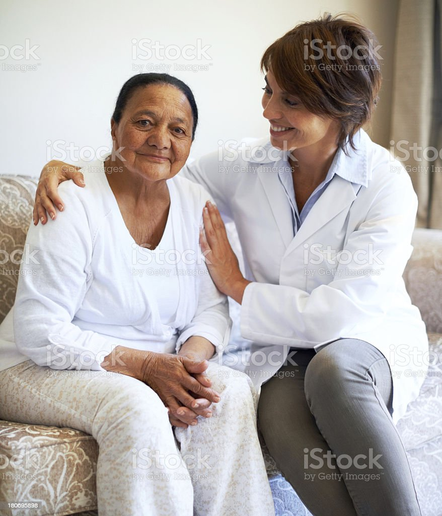 Mature woman on a sofa with doctor royalty-free stock photo