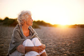 istock Mature woman on beach looking into horizon 486858785