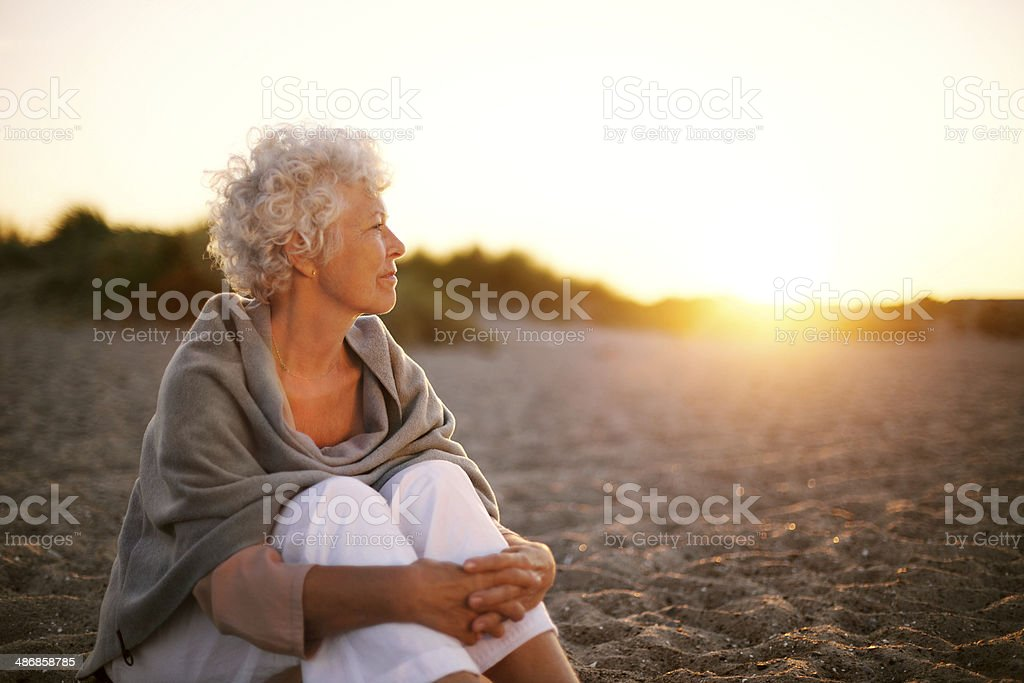 Mature woman on beach looking into horizon stock photo
