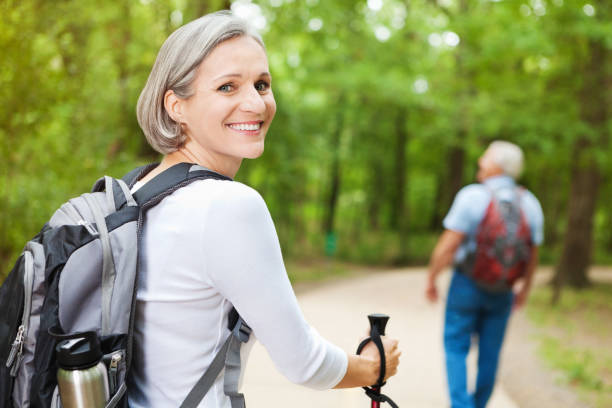 mature woman on hiking trip with husband - woman portrait forest foto e immagini stock
