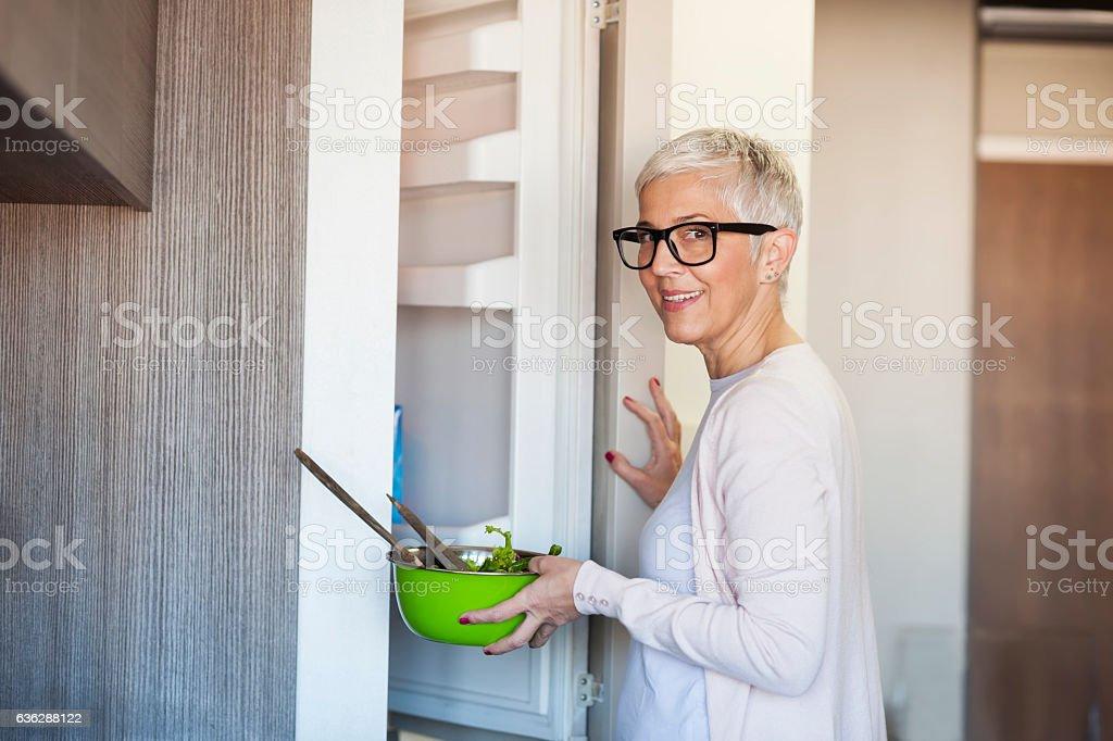 Mature woman opening refridgerator stock photo