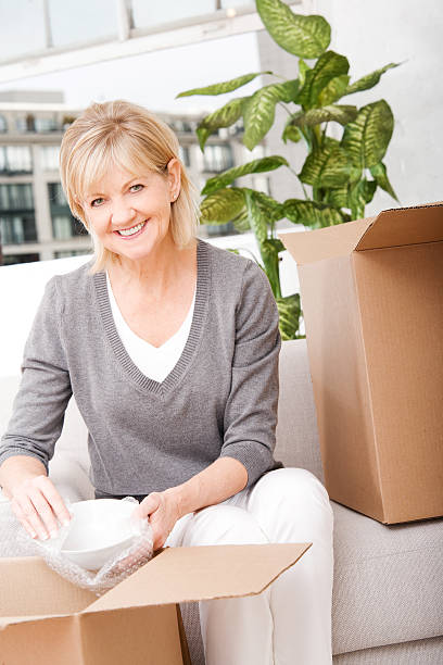 Mature Woman Packing or Unpacking Boxes at Home stock photo