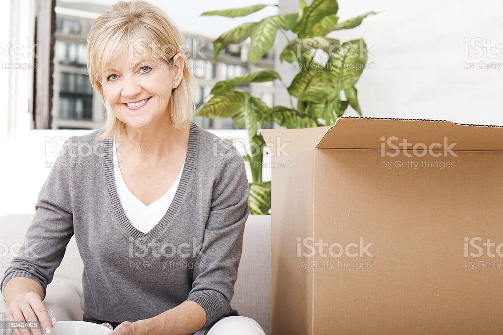 Mature Woman Packing or Unpacking Boxes at Home royalty-free stock photo