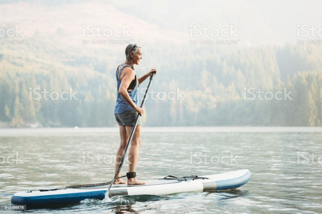 Mature Woman Paddleboarding stock photo