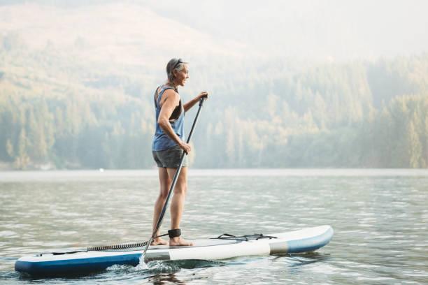 reife frau paddling - stehpaddeln stock-fotos und bilder