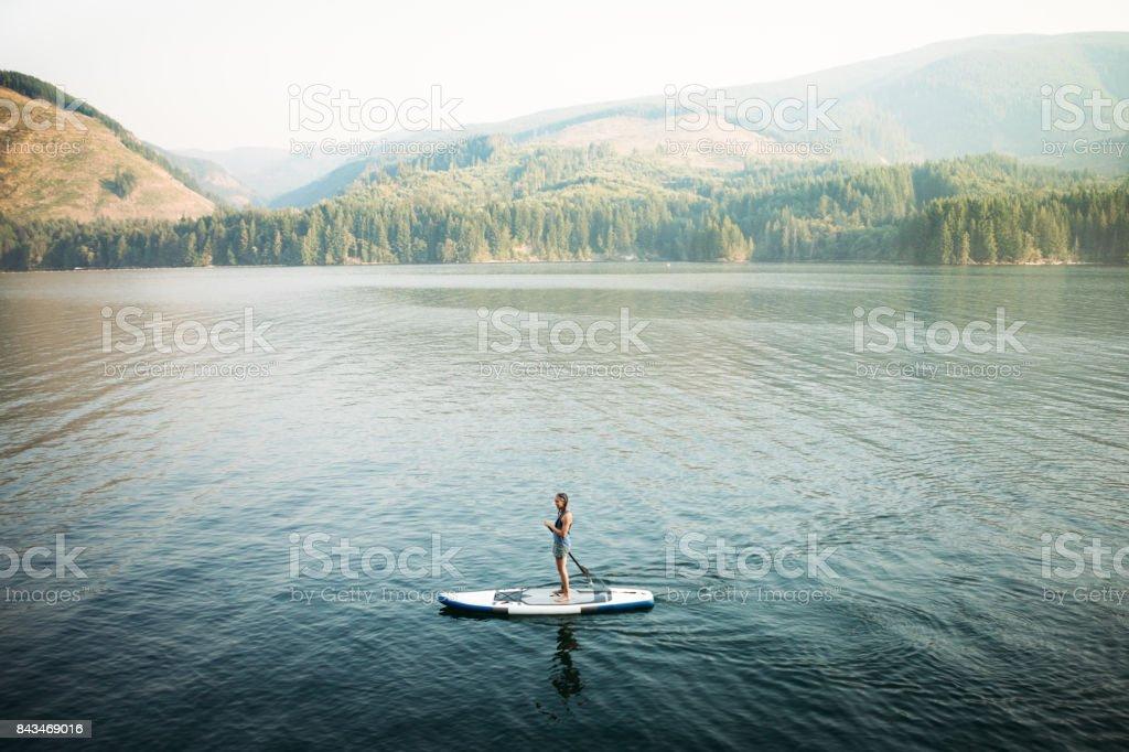 Mature Woman Paddleboarding stock photo