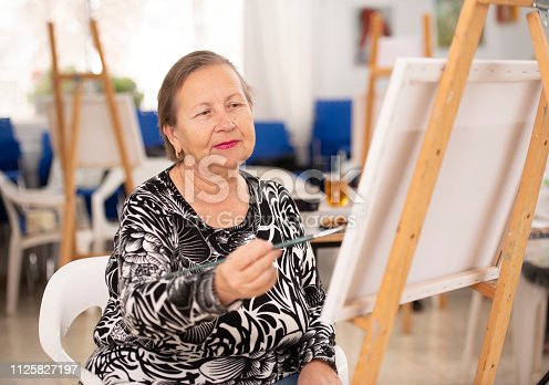 585509074 istock photo Mature woman painting on canvas. 1125827197