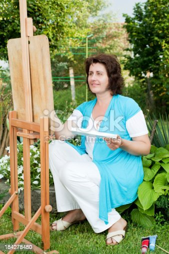 585509074 istock photo Mature woman painting outdoors. 184278480