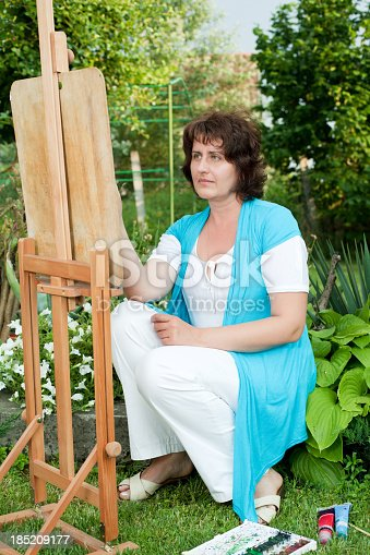 585509074 istock photo Mature woman painting outdoors. 185209177