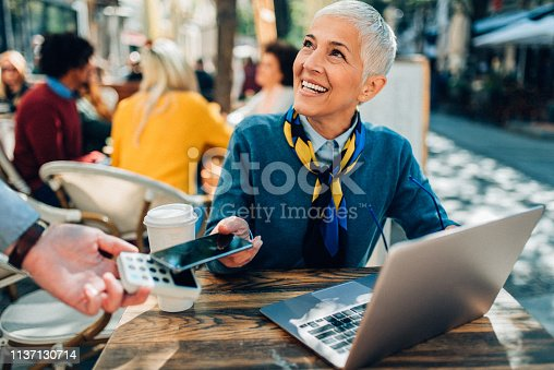 Mature elegant woman paying contactless with smartphone in sidewalk cafe