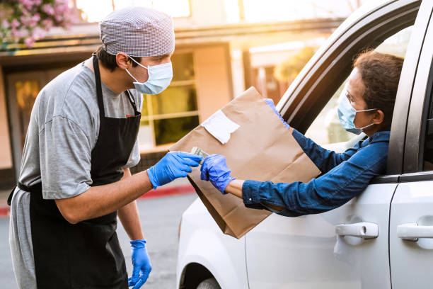 Mature woman picking her restaurant food from her car at a Curbside pickup Caucasian mature woman picking her restaurant food from her car at a Curbside pickup curbsidepickup stock pictures, royalty-free photos & images