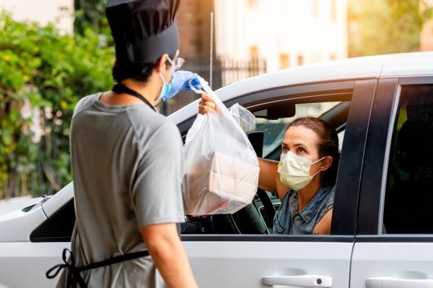 mature woman picking her restaurant food from her car at a pick up curve - prevenzione delle malattie foto e immagini stock